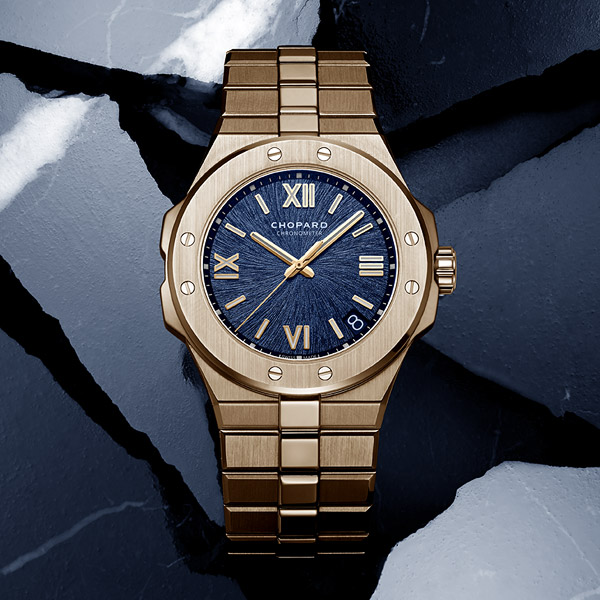 The Alpine watch in rose gold and blue dial set on a rock gray background