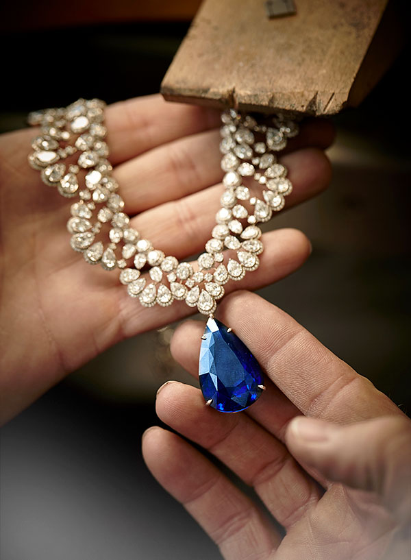 Close-up of two hands holding a magnificent necklace ornated with a royal blue sapphire.