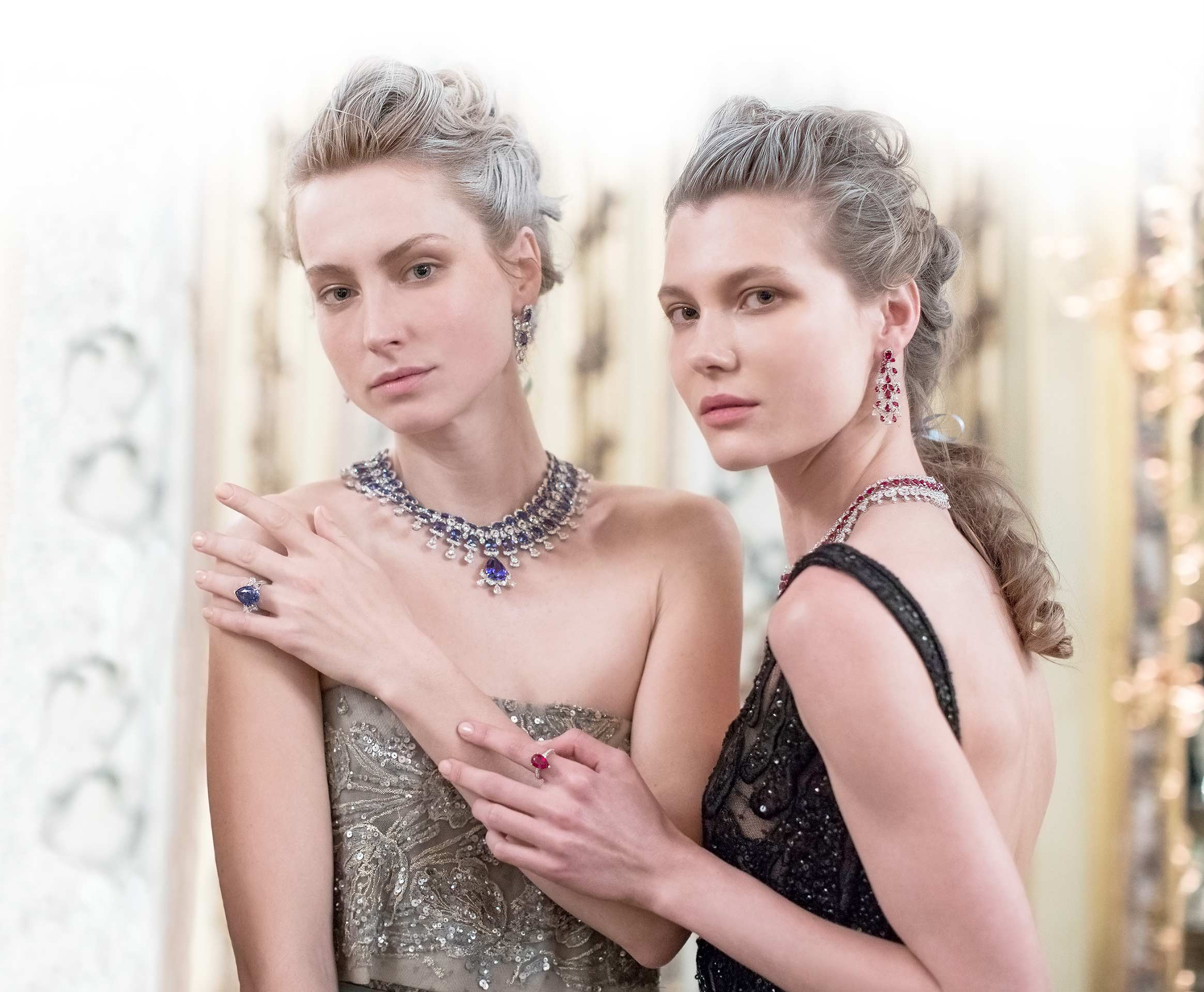 Two women wearing elegant dresses and the precious lace collection pieces.