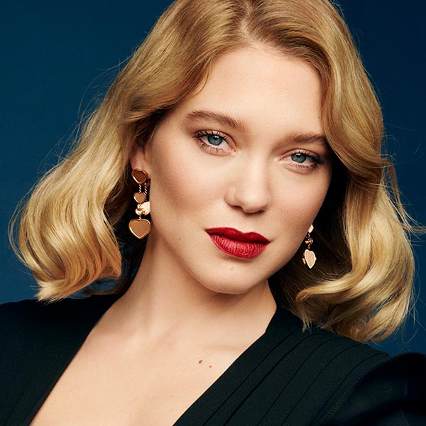 Léa Seydoux facing the camera and wearing happy hearts earrings