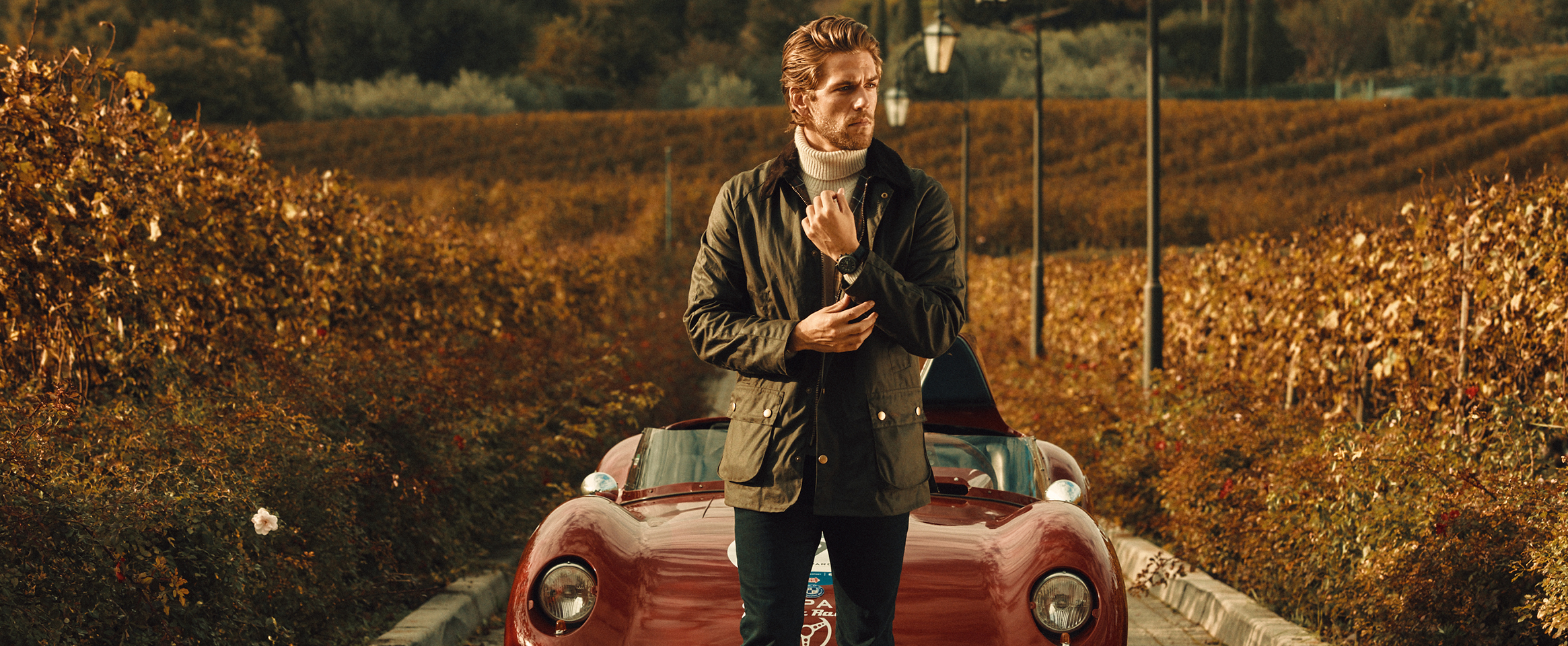 A man in the middle of a vineyard during autumn, wearing a watch from the Mille Miglia Collection