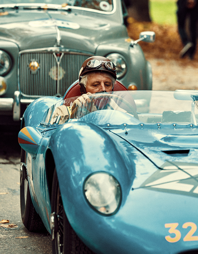 A couple driving an ancient collection light blue automotive during a race.