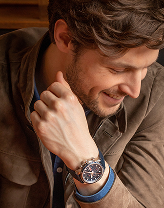 An elegant man wearing a watch from the Mille Miglia Collection. He is looking down, smiling.