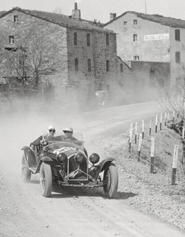 Black and white illustration of a couple racing with an antic automotive, supported by a crowd