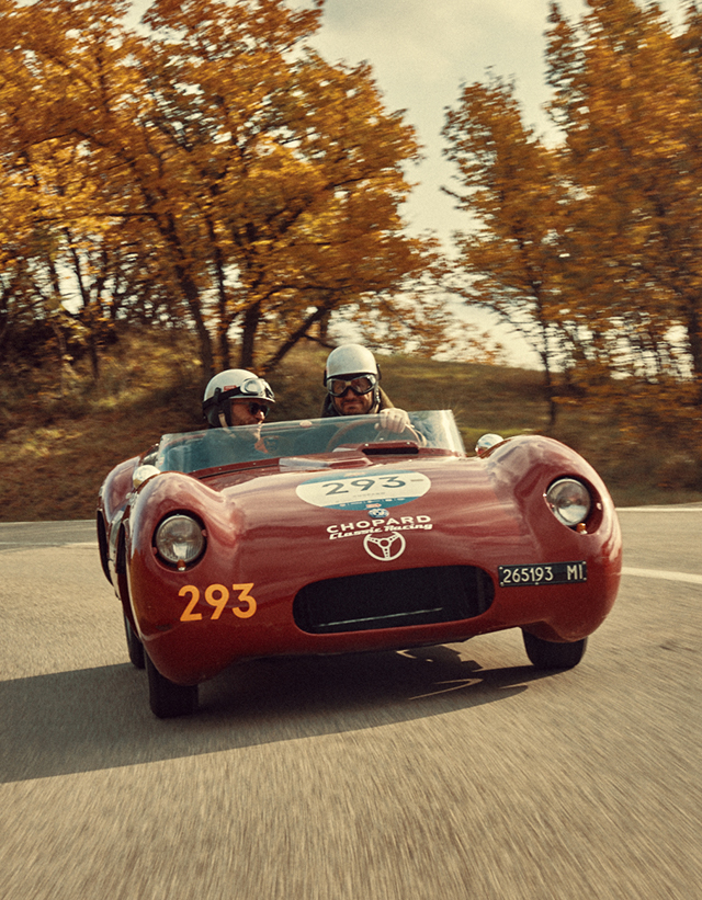A red ancient racing car taking a turn on a countryside road, surrounded by trees with autumn leaves