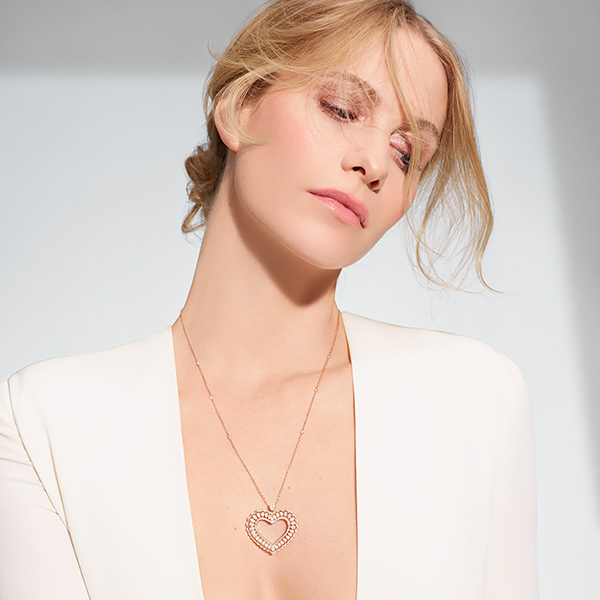 Poppy Deleving wearing a white dress and the Prcious Lace Jewellery in white gold and diamonds.