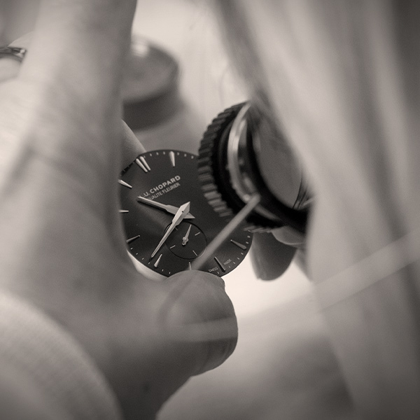 Close-up in black and white on the hand of a Chopard craftswoman who checks the quality of the LUC watch.