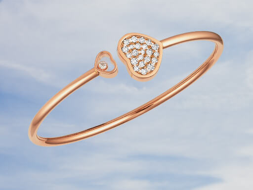 A shiny Happy Hearts bangle on a sky-blue background.
