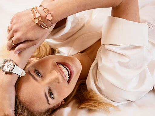 A cheerful woman laying on her back wearing the Happy Sport watch, and bracelets and bangles from the Happy Diamond Collection.