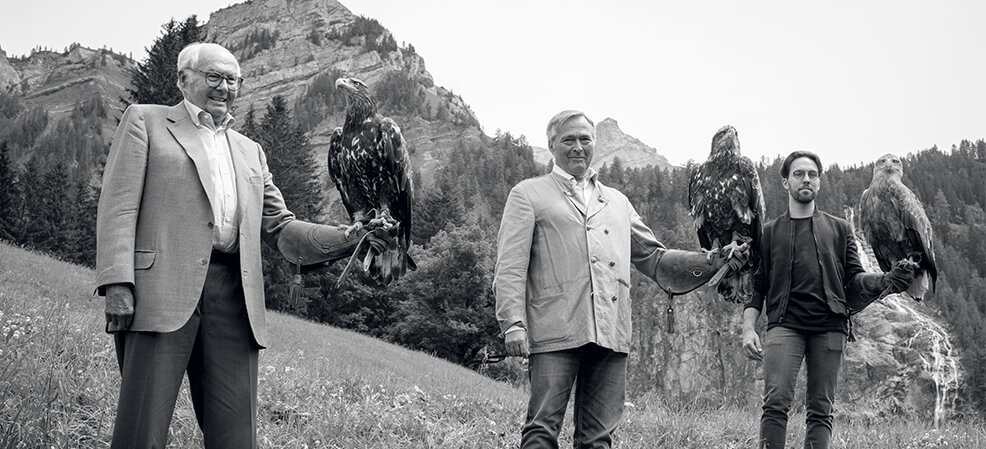 3 generations of Scheufele (son, father and grandfather) each holding an eagle on their left hand in the Alps.