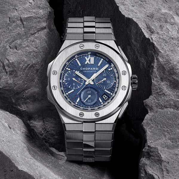 The Alpine XL Chrono in stainless steel and blue dial set on a rock gray background