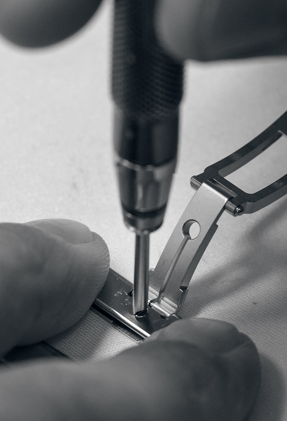 Close-up view of a Chopard employee's fingers as he works on a watch bracelet.