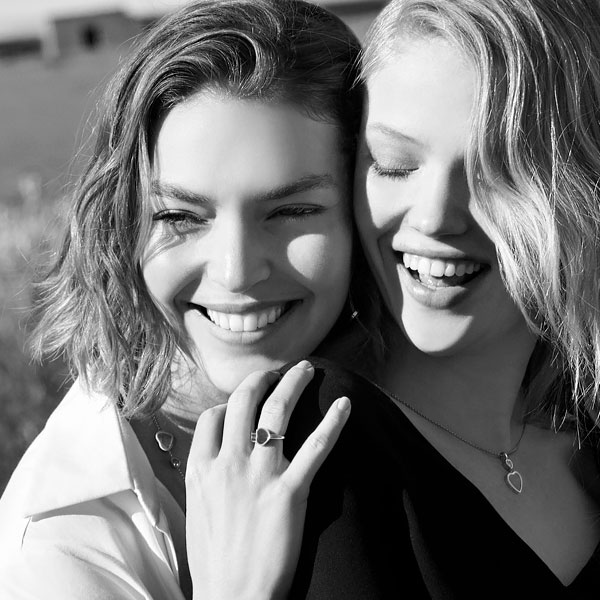 Picture in black and white of two women laughing together and wearing Happy Hearts Jewellery