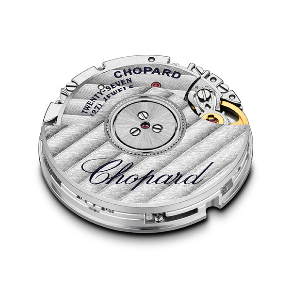 A silvery watch movement, engraved with Chopard's name.