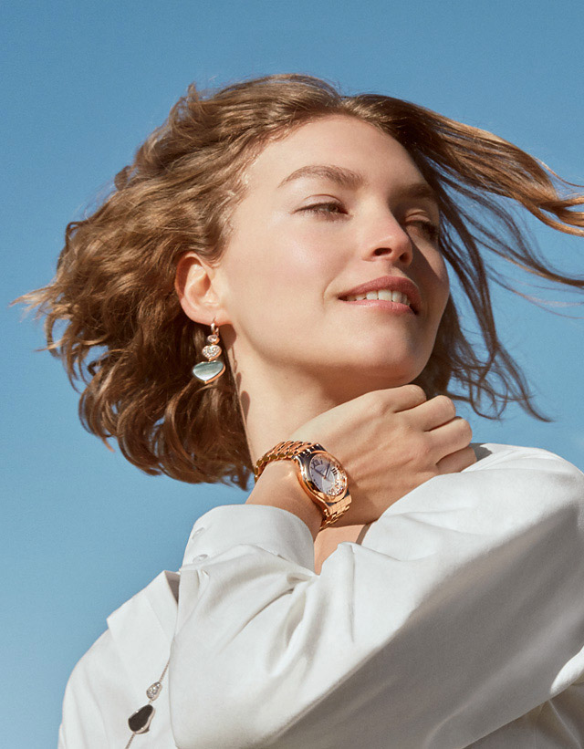 Woman in a white shirt wearing an 18k rose gold Happy Sport Oval watch on her left wrist and Happy Hearts earrings.