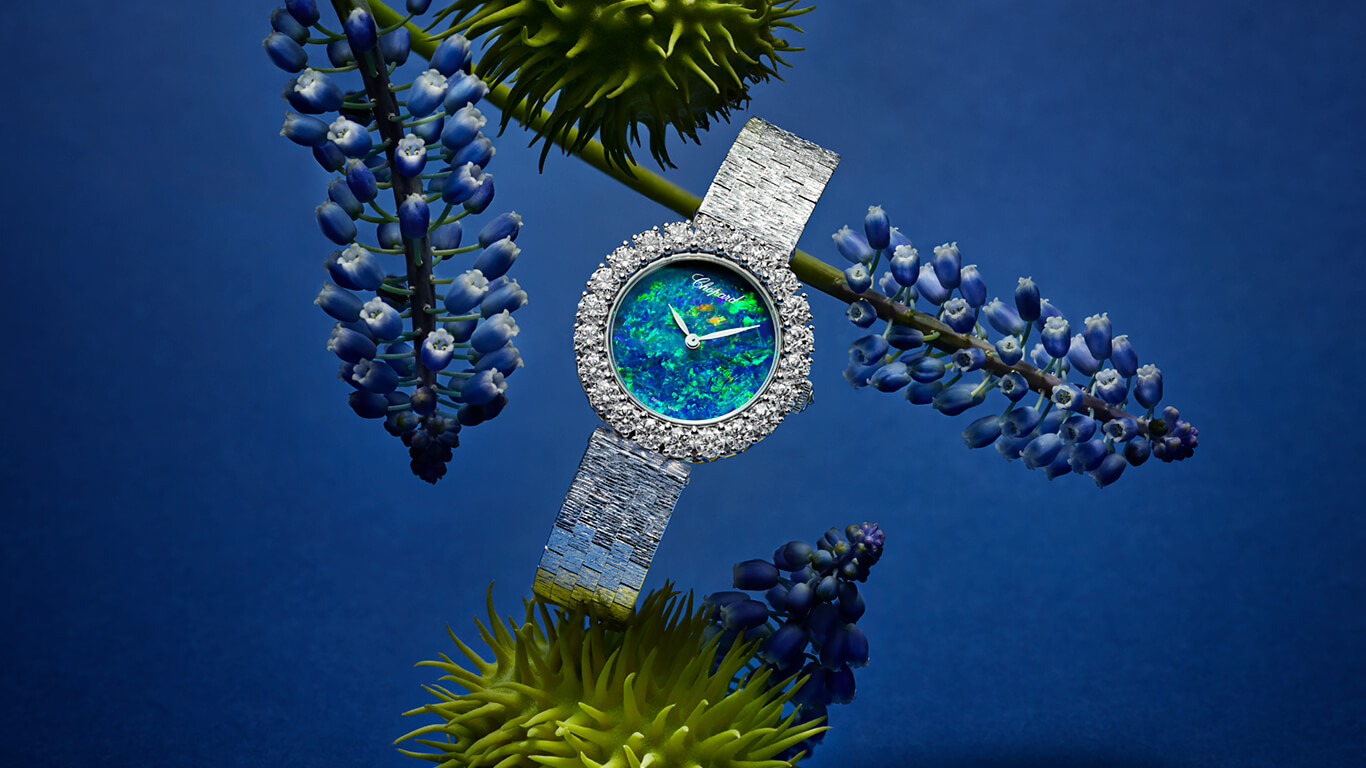 L'Heure du Diamant watch hanging on blue and geen flowers