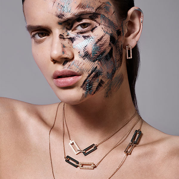 Close-up of a woman wearing stylized make-up on the left side of her face, as well as 3 Ice Cube Two Tones necklaces.