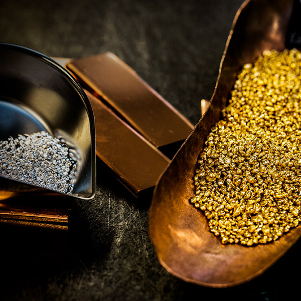 Hundreds of responsibly-sourced gold nibs in two coppery scoops, with two gold bars inbetween them.