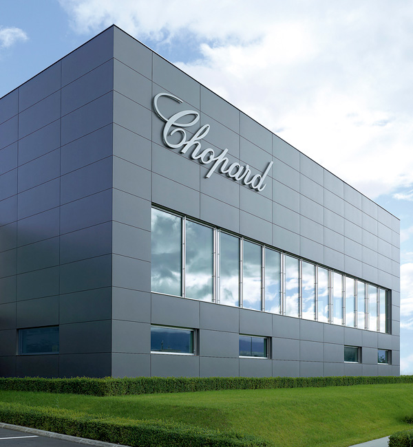A big, modern, grey production building belonging to Chopard, with the company name written in big on it.