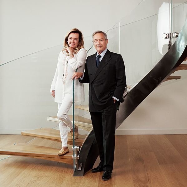 Karl-Friedrich and Caroline Scheufele posing in front of stairs with glass handrail and wooden steps.