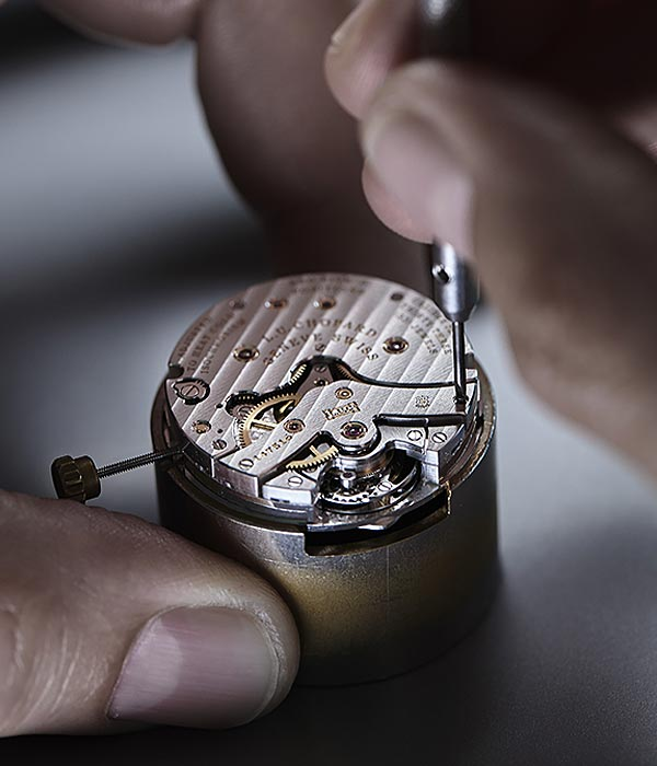 Watch movement from close, with someone working on it and holding it with the fingers, showing how tiny the movement is.