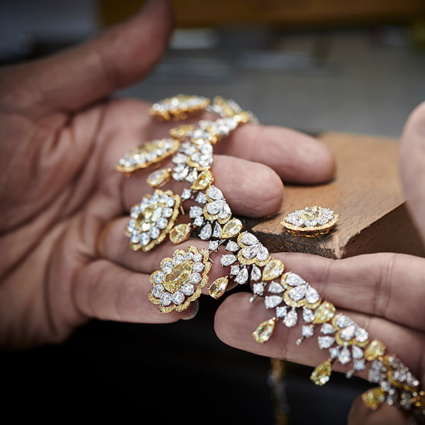 Two hands holding a finely crafted necklace of gold and diamonds.