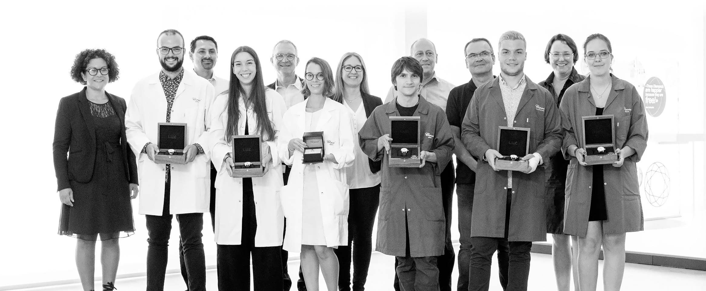 13 employees of Chopard, some wearing blouses and holding Chopard watches in their boxes in their hands.
