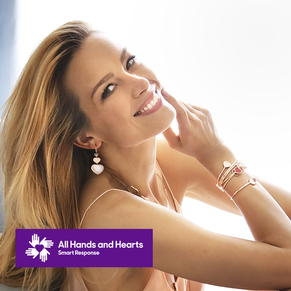 Petra Nemcova wearing Happy Hearts armwrists and earrings in front of a white background.