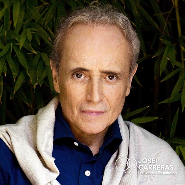 José Carreras in a blue shirt with a grey scraf on the shoulder.