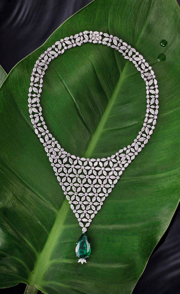 Necklace (with flowers patterns and a green emerald) resting on a big banana leaf.