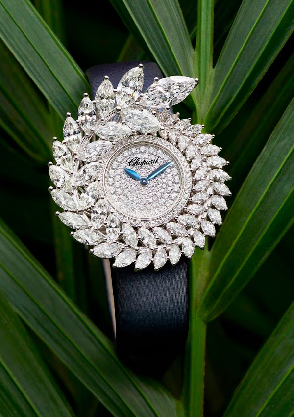 Watch made out of diamonds shaped like a palm, with light blue needles and a black leather strap, resting over a big fern.