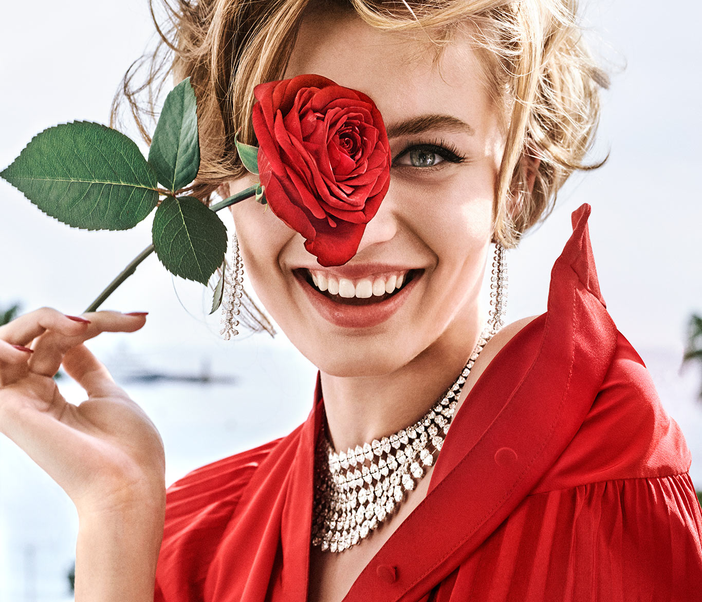 Young smiling lady holding a rose on her face and wearing Chopard high jewellery