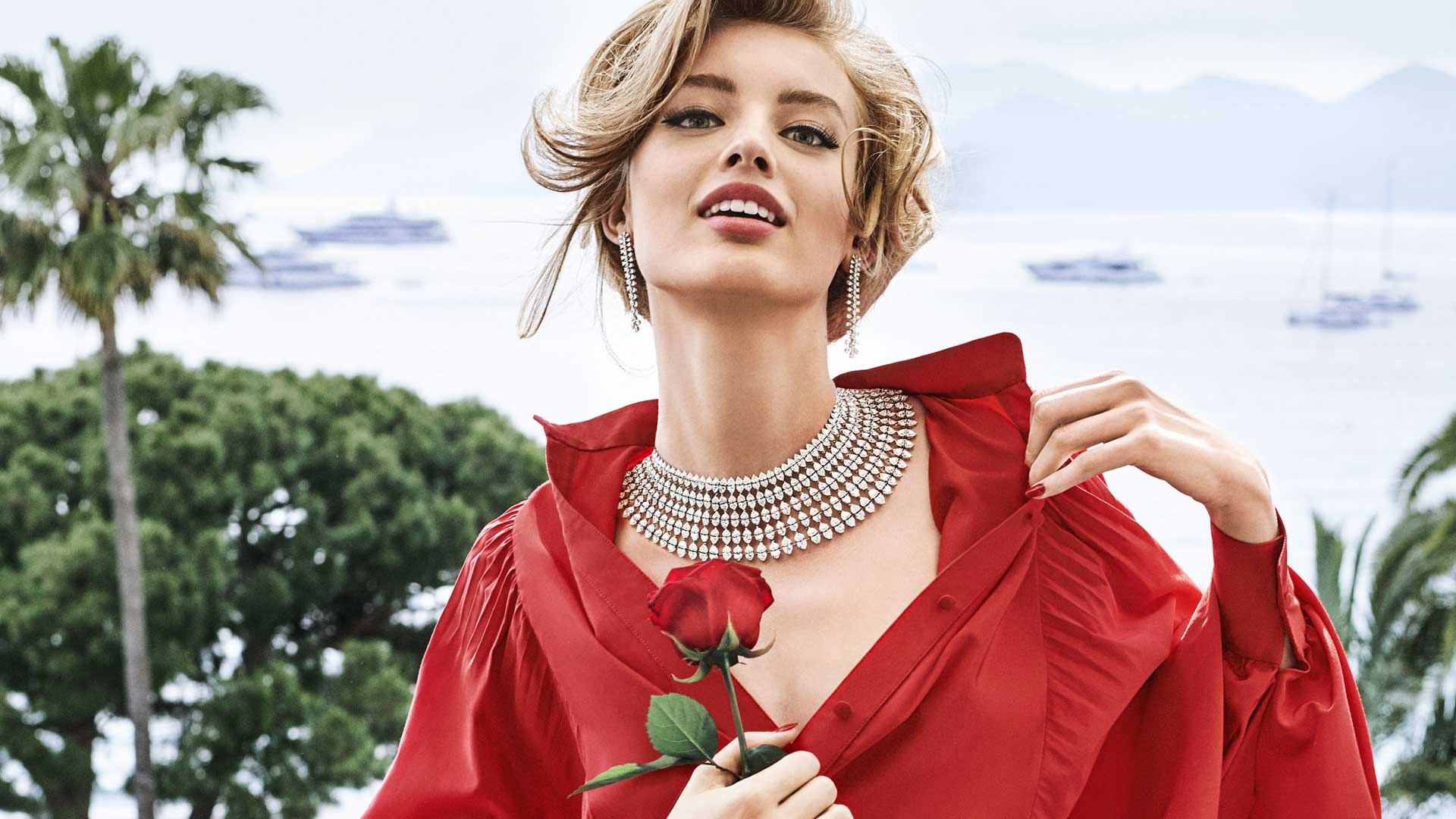 Young blond lady wearing Chopard high jewellery and holding a red rose.