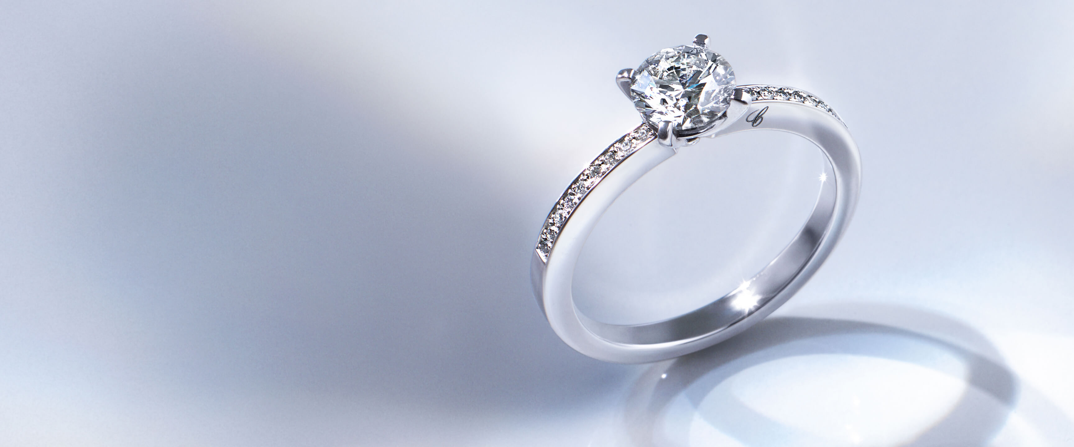 close- up view of diamond solitaire with a semi paved band and Chopard C engraved on side