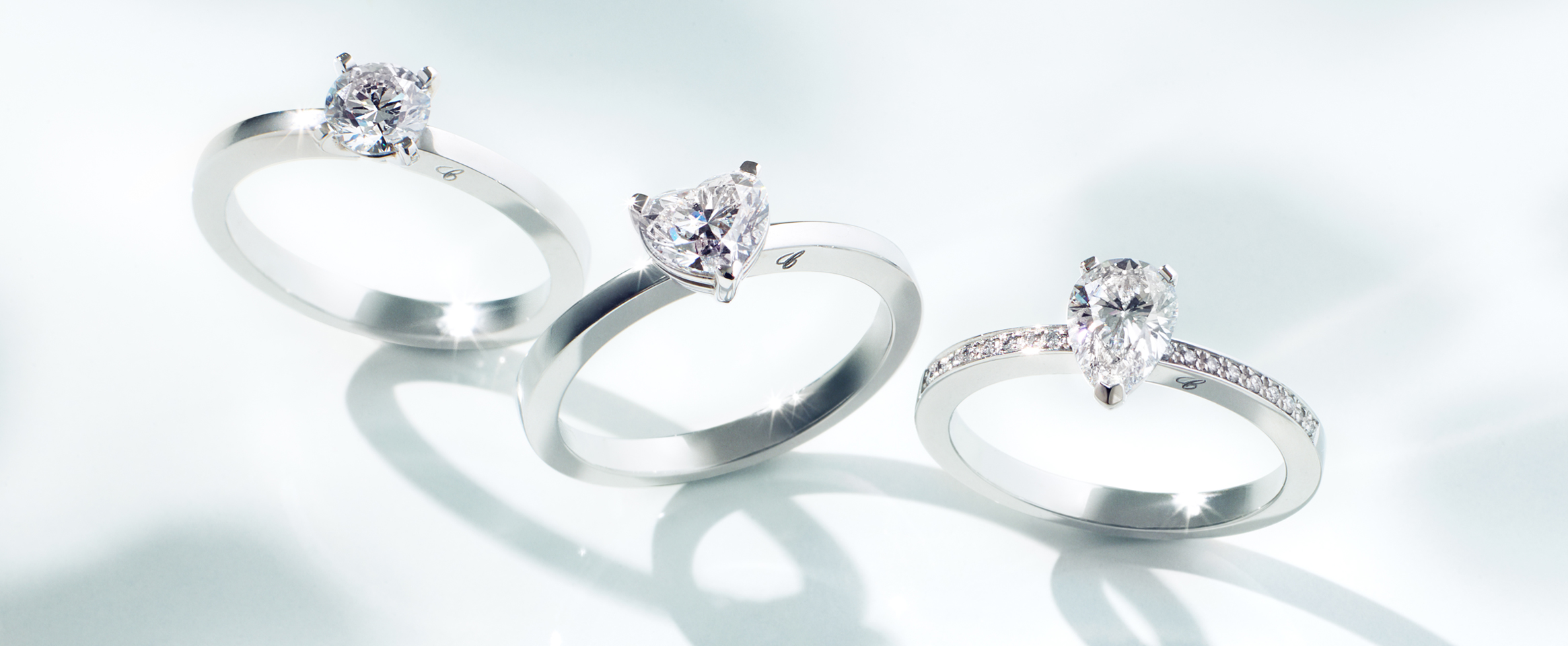 close-up view of 3 platinum solitaires engagement rings with 3 different diamond cuts, round, heart and pear