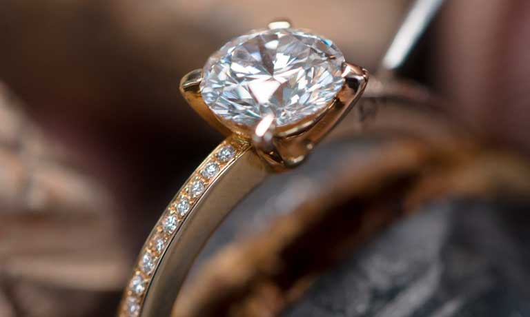 Image of a diamond solitaire ring with micro paved band