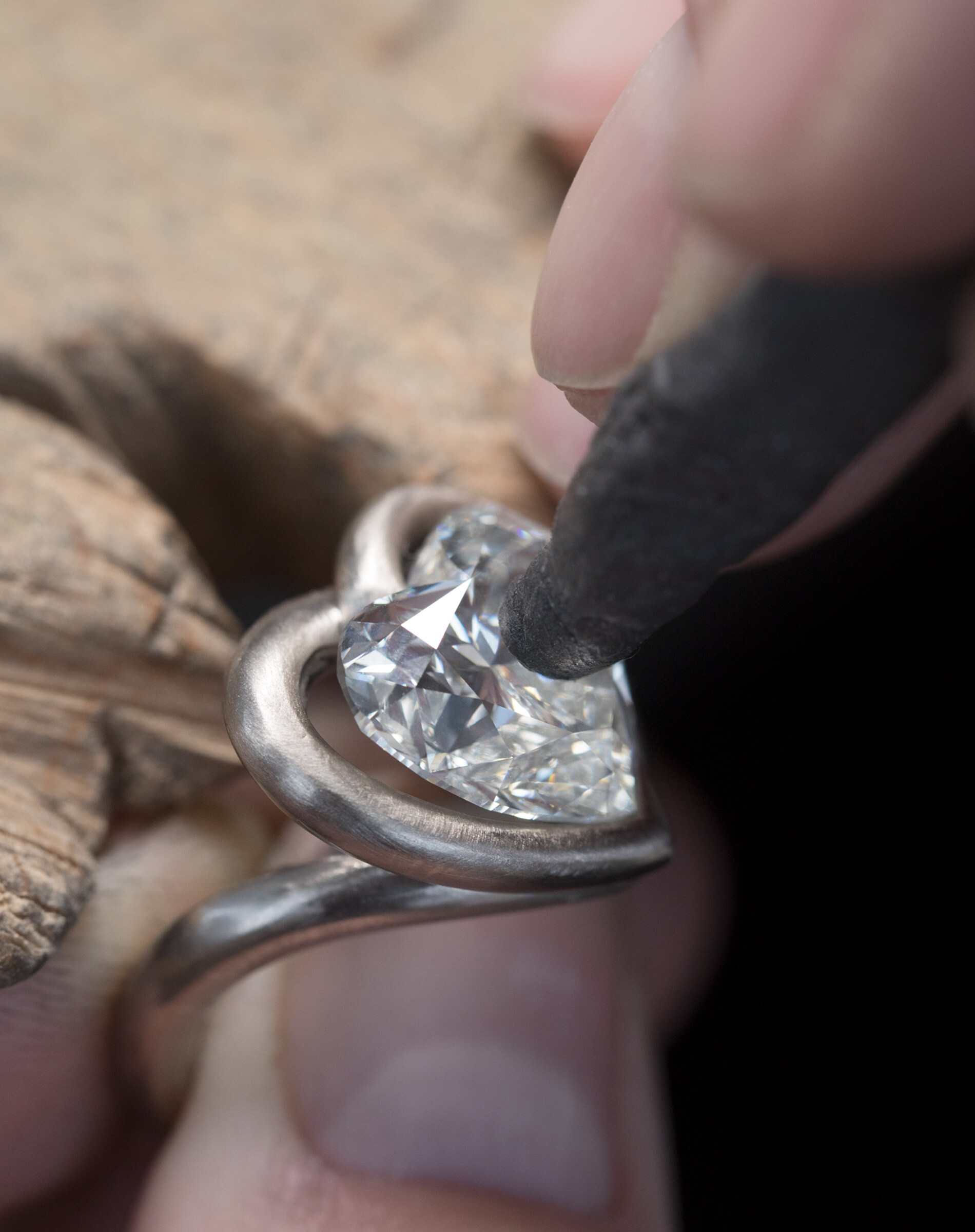 Image of artisan setting a heart shaped stone into place