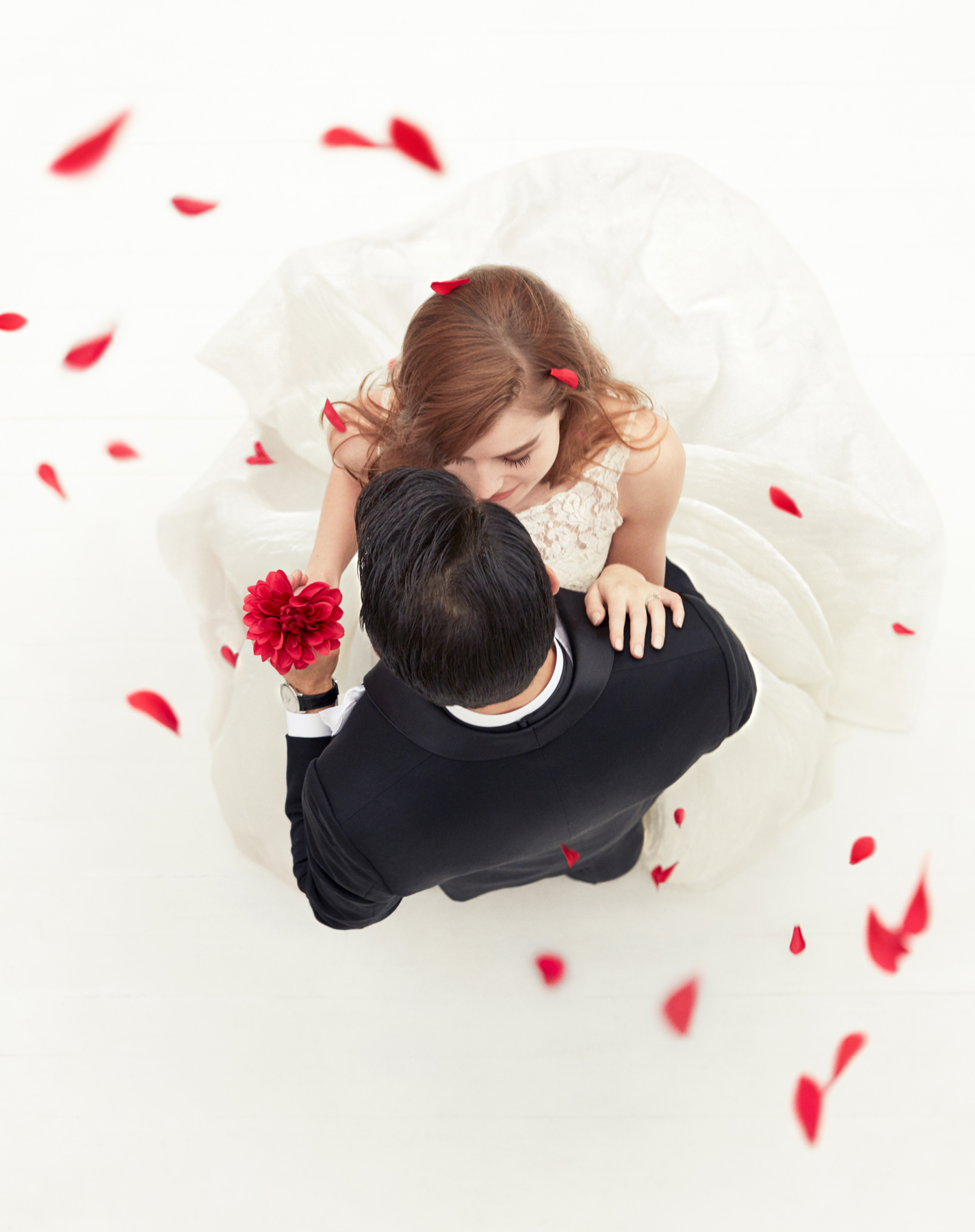 overhead image of bridal couple dancing surrounded by red flower petals
