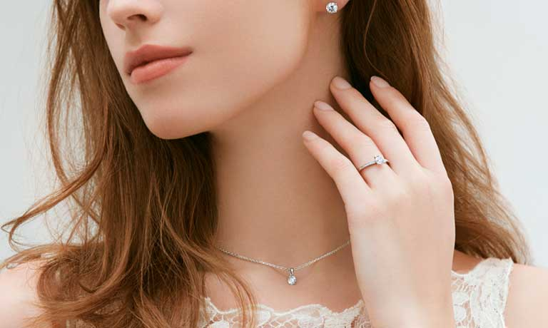 Image of model wearing diamond earrings a diamond ring and a diamond necklace