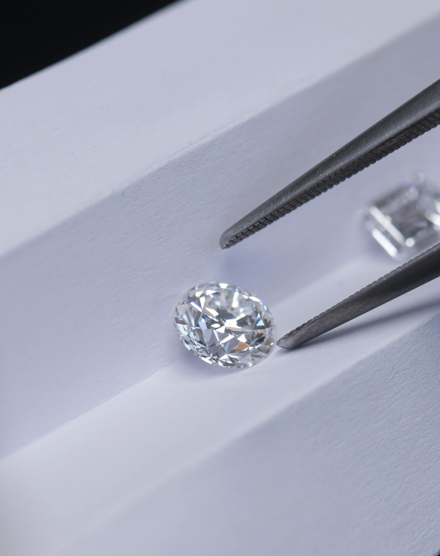 Close-up view of diamonds on a white paper being sorted with a pair of tweezers