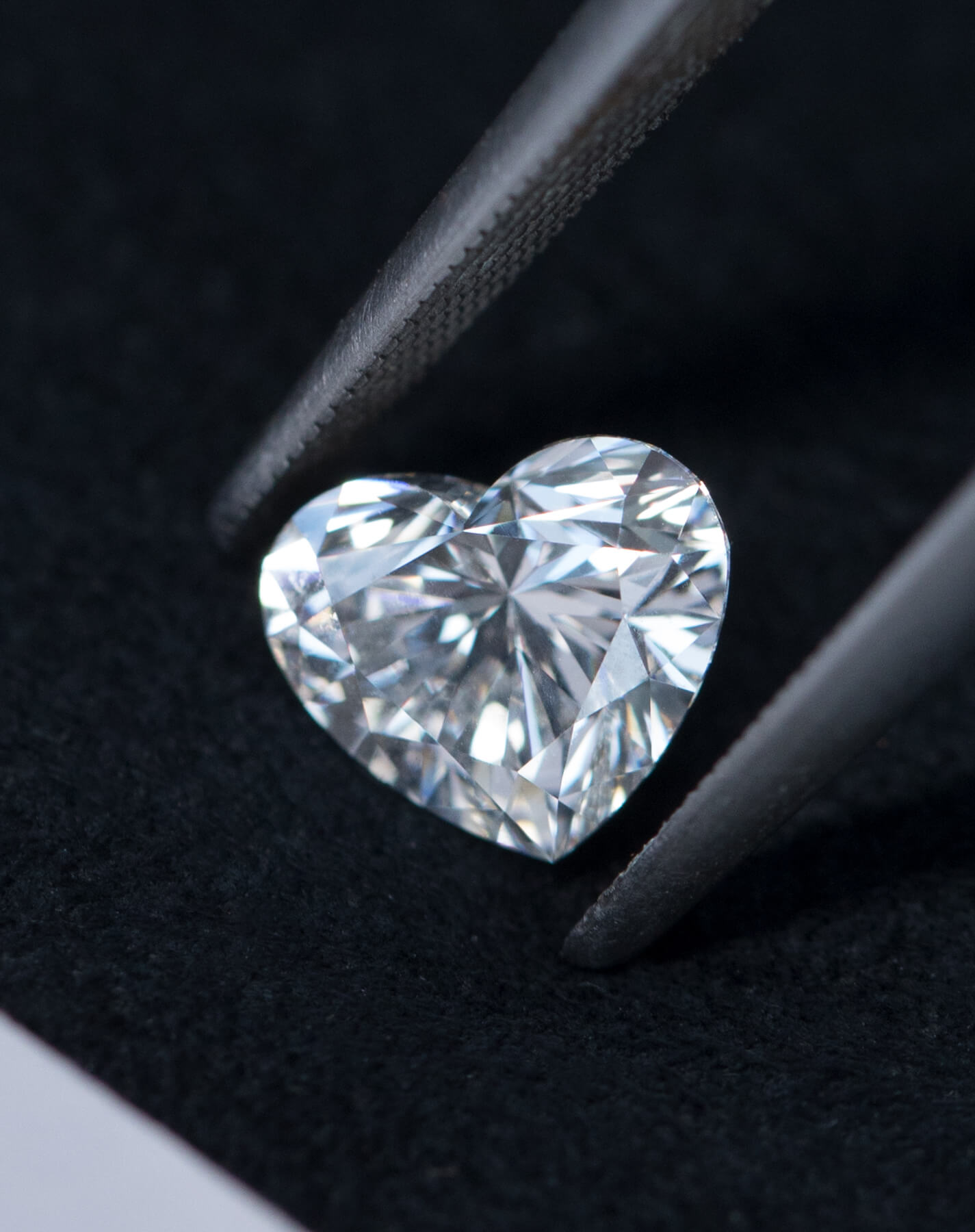 Image of heart shaped diamond being held by a pair of tweezers