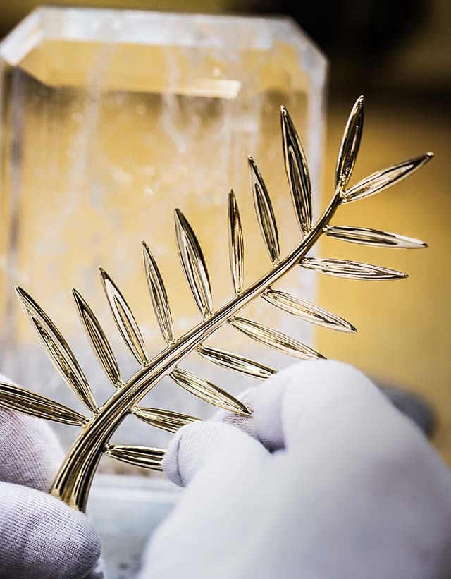 Hands holding the Fairmined gold Palme d'or trophy in the making