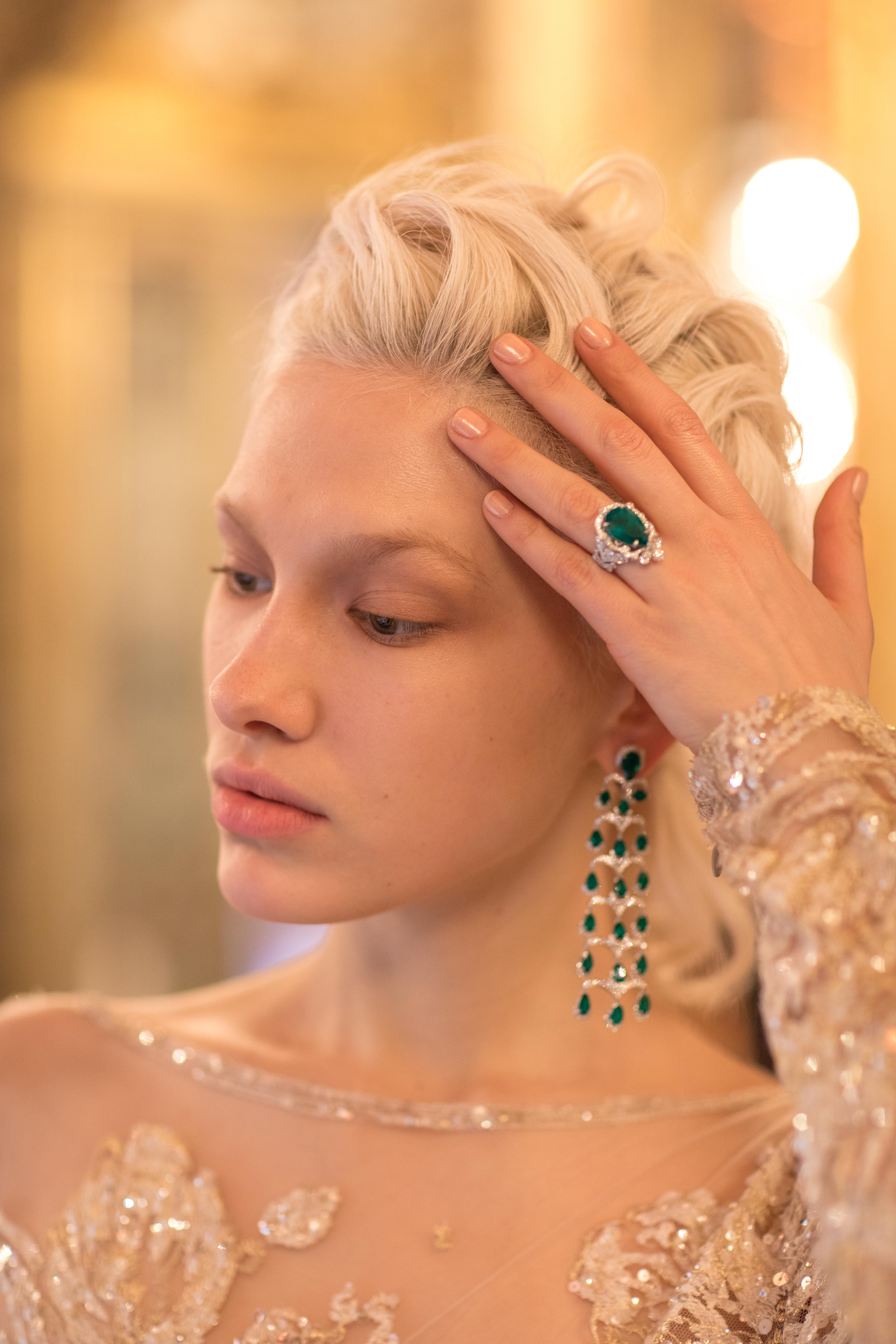 Image of model wearing emerald and Diamond chandelier earrings and emerald and Diamond ring
