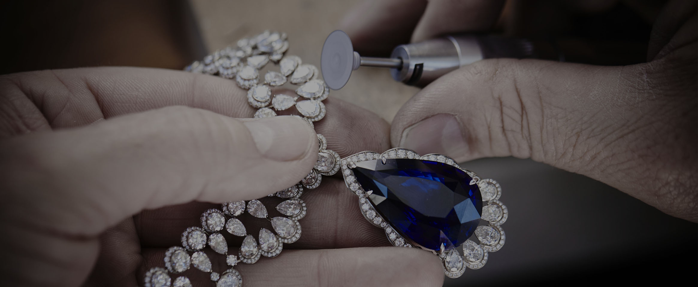 Image of artisan polishing Diamond and Sapphire necklace