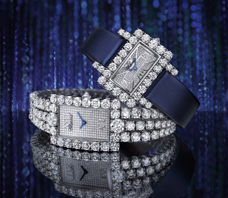 Image of 2 Heure du Diamant watches, one with Diamond bezel and blue satin strap the second with paved diamond bezel and diamond paved strap and