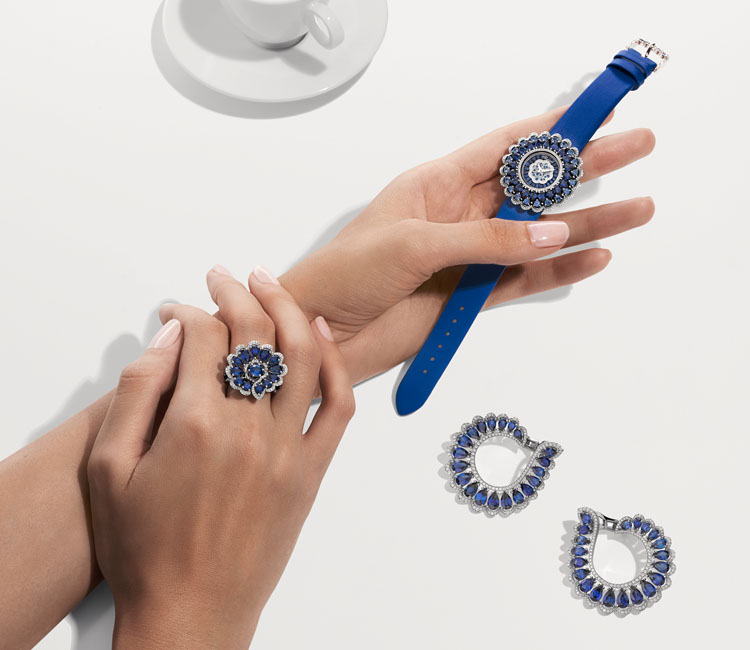 Image of woman wearing diamond and sapphire ring while holding a matching watch on satin strap alongside matching hoop style earrings
