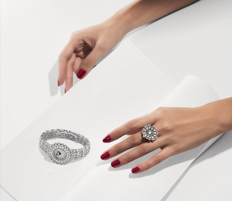 Image of woman's hands wearing a diamond paved precious collection ring reaching for a fully paved diamond watch