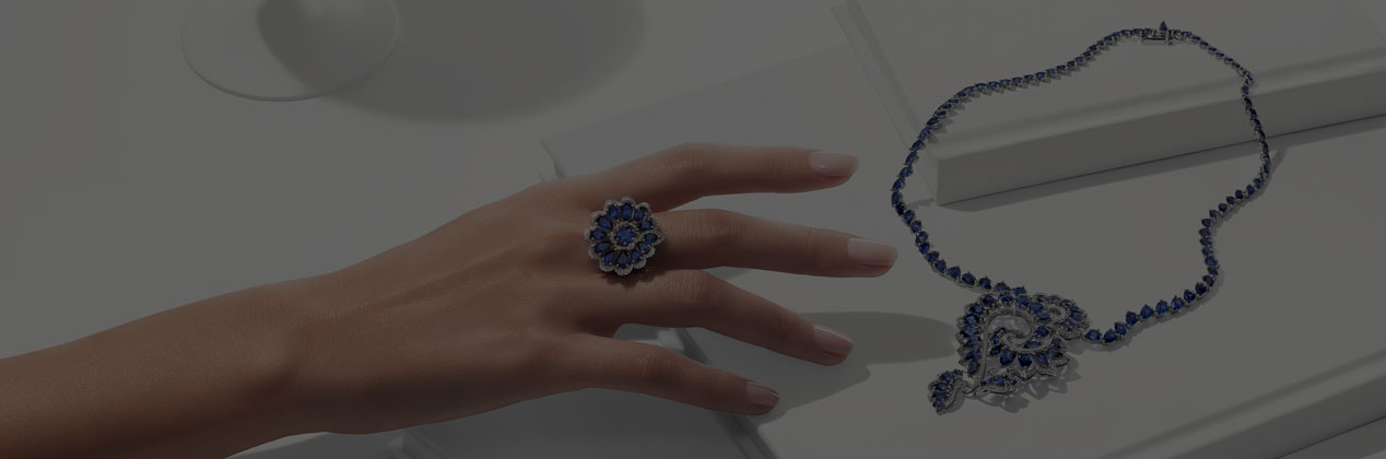 veiled image of a woman's hand wearing a diamond and sapphire ring reaching for a diamond and sapphire necklace