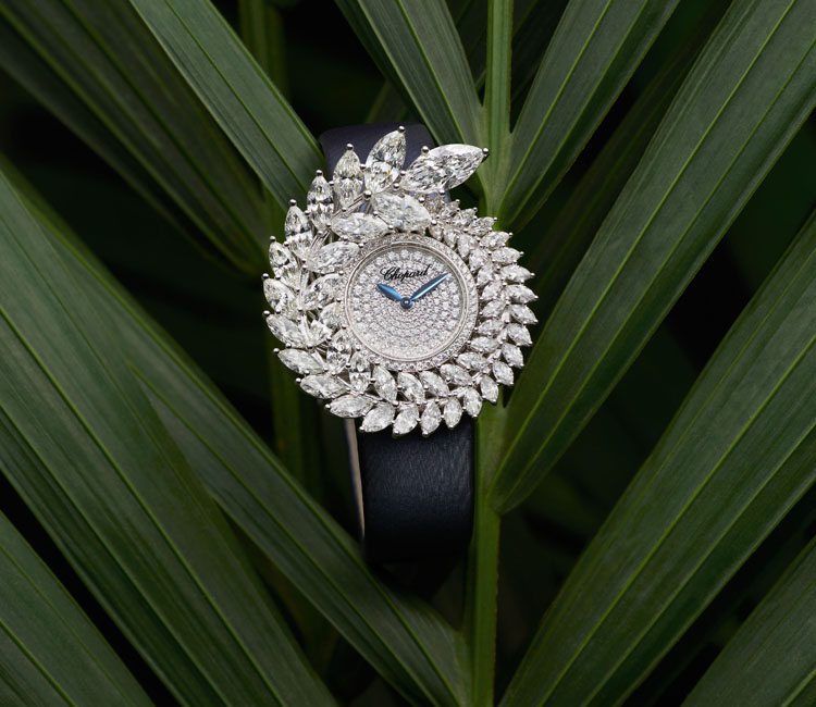 Close-up image of Green carpet collection Diamond paved watch on black satin strap over a green palm leaf