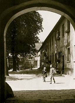 Black and white Image of Children walking in a courtyard